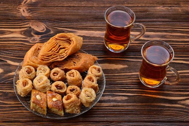 Турецкая сладкая пахлава на тарелке с турецким чаем.