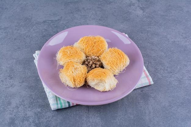돌 표면에 보라색 접시에 pinecones와 터키어 달콤한 디저트