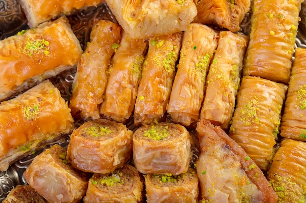 トルコのお菓子バクラヴァと木製の背景に金属東洋トレイ