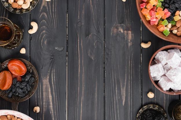 Turkish tea; dried fruits; raisins; nuts and lukum on black textured wooden desk