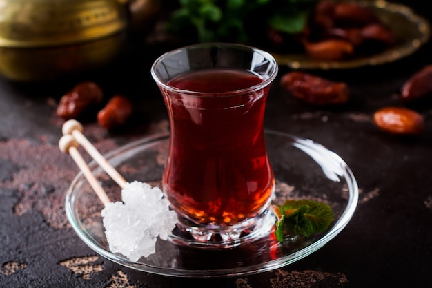 Турецкий чай в традиционной стеклянной чашке с карамелизированным сахаром и мятой на темном фоне