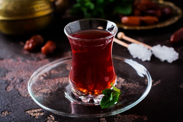Турецкий чай в традиционной стеклянной чашке с карамелизированным сахаром и мятой на темном