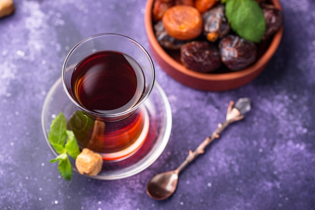 Turkish tea in traditional glass with dried fruits