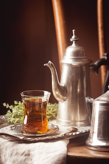 Turkish tea in traditional glass with kettle on metal tray.