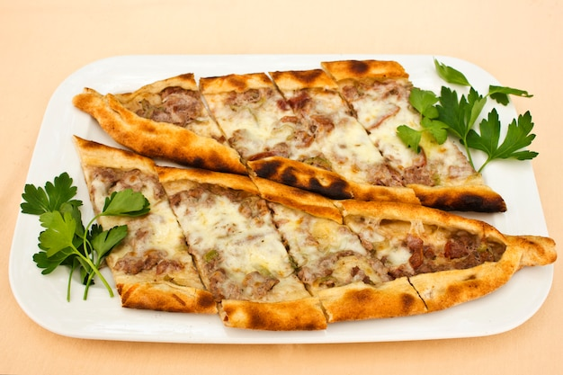 Turkish tortilla pita with pieces of meat, melted cheese and slices of vegetables