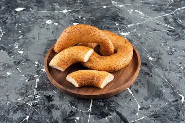 Simit bagel tradizionale turco in un piatto di legno su uno sfondo di marmo.
