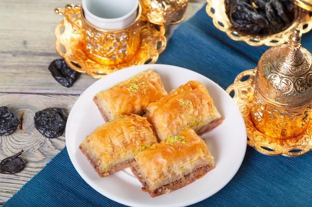 Turkish traditional dessert baklava with tea on dark.
