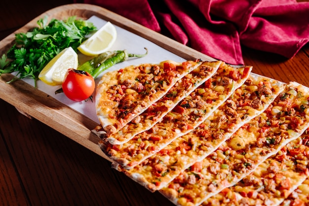 Turkish traditional lahmacun with green salad, lemon and tomato inside wooden plate.