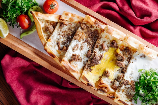Turkish traditional lahmacun with meat and cheese stuffing served inside wooden platter.