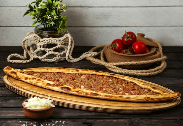 Turkish traditional pide with cheese and stuffed meat on a wooden board