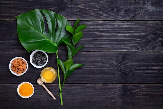 Куркума, миндаль, семена подсолнечника и мед на черном фоне. концепция повышения иммунитета. копировать пространство