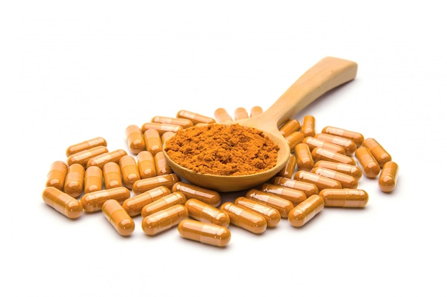 Turmeric capsules and powder in a wooden spoon.