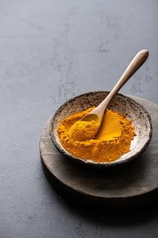 Turmeric or curcuma in a ceramic bowl, indian spices, selective focus