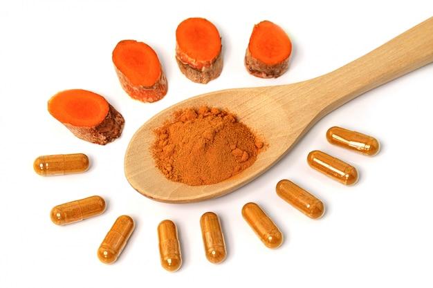 ウコン(curcuma longa l.)またはcurcuma longaパウダー、白い壁、スパ製品、食品成分、ハーブカプセルに分離された代替医療用カプセル。