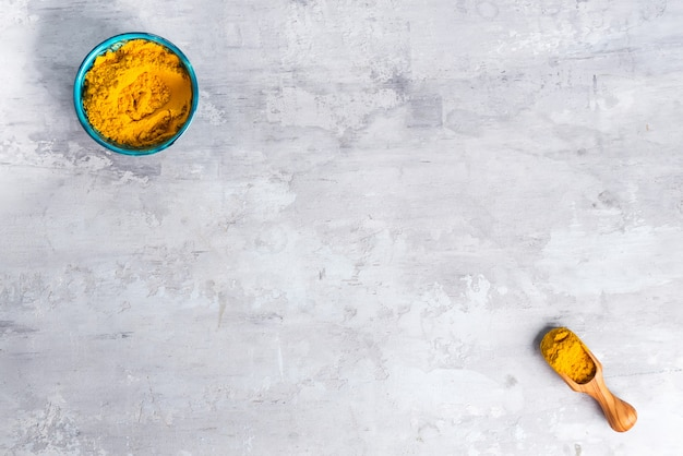 Turmeric curcuma powder pile on stone background, top view