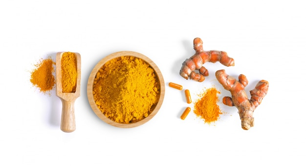 Turmeric (curcuma) powder pile in wood bowl  and capsule isolated on white space