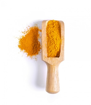Turmeric (curcuma) powder pile in wood scoop isolated on white surface, top view