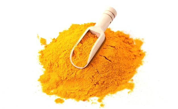 Turmeric or curcuma powder with wooden scoop isolated on white background