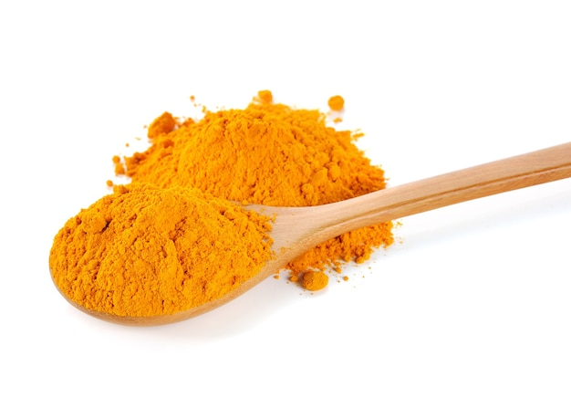 Turmeric (curcuma) powder on wooden spoon isolated on white background.