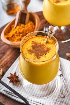 シナモンスティックとハチミツを添えたターメリックゴールデンミルクラテ。健康的なアーユルヴェーダドリンク。ビーガン向けのスパイスを使ったトレンディなアジアのナチュラルデトックス飲料。スペースをコピーします。