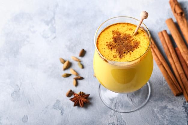 Золотисто-молочный латте с куркумой, палочками корицы и медом. здоровый аюрведический напиток. модный азиатский натуральный детокс-напиток со специями для веганов. скопируйте пространство.