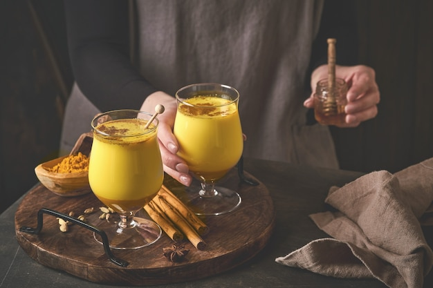 Turmeric golden milk latte with cinnamon sticks and honey. healthy ayurvedic drink. trendy asian natural detox beverage with spices for vegans. copy space.