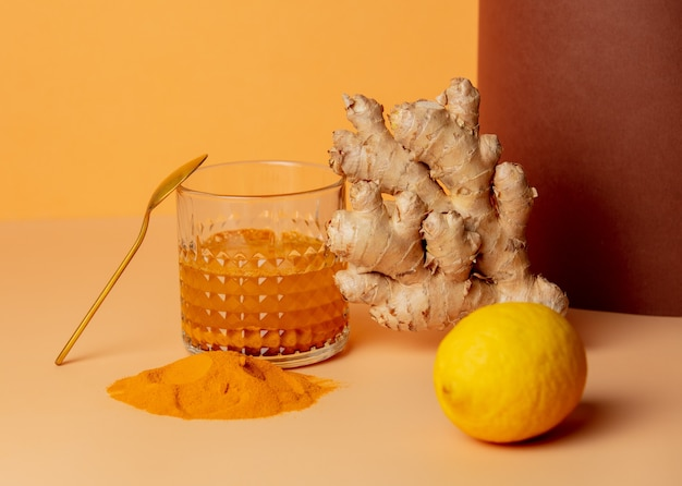 紙の上のガラスの横にウコン、蜂蜜、レモン、生姜