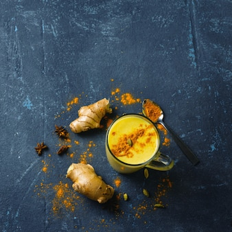 Turmeric latte on black background with copy space top view