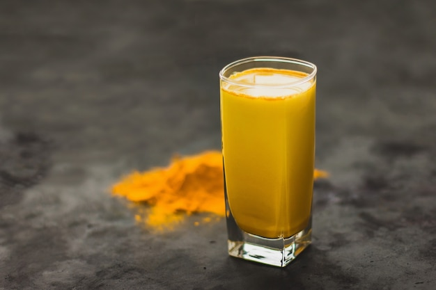 Turmeric latte, a golden milky hot healthy drink on a dark background in a glass tumbler