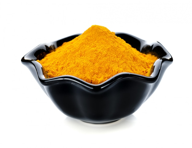 Turmeric powder in bowl isolated on white
