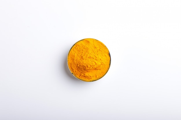 Turmeric powder in bowl over white background.