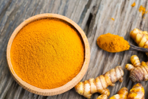 Turmeric powder in bowls and fresh turmeric on old wooden table. herbal