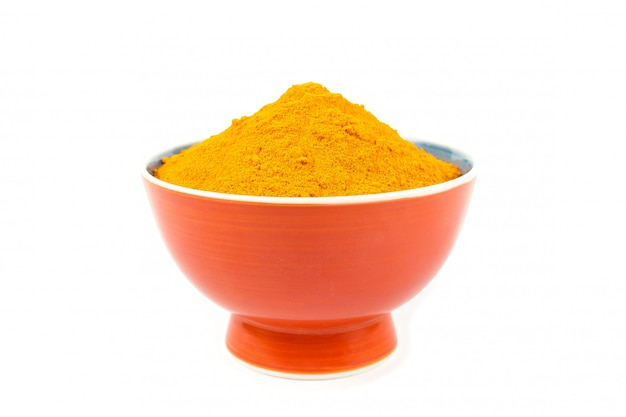 Turmeric powder (curcuma) in brown bowl on white background. herbal