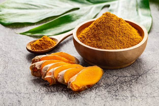 Turmeric powder and fresh slices of turmeric root on grey