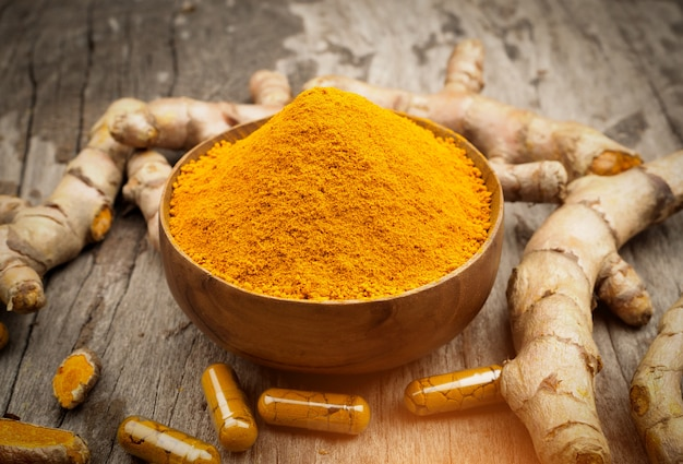 Turmeric powder and fresh turemric in wood bowls on wooden table. herbs are native to southeast asia.