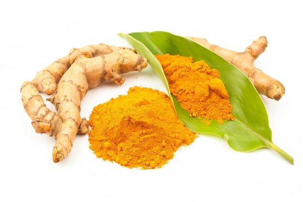 Turmeric powder and fresh turmeric (curcuma) with green leaf on white background. herbal