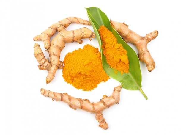 Turmeric powder and fresh turmeric (curcuma) with green leaf on white background