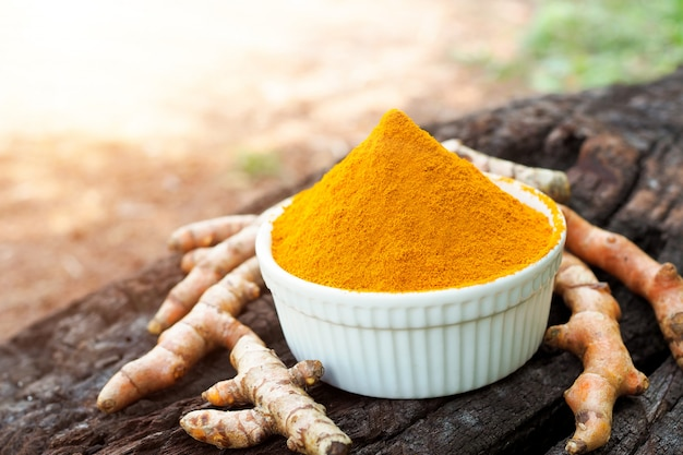 Turmeric powder and fresh turmeric in white bowls on old wooden telble. herbal