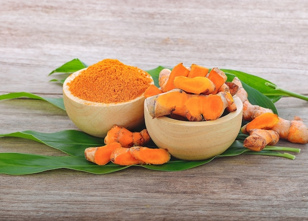 Turmeric powder and fresh turmeric on wooden background.herb high vitamin c and protect virus.