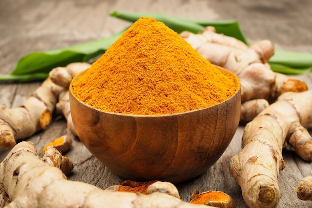 Turmeric powder and fresh turmeric in wooden bowls with green leaf on old wooden table. herbs