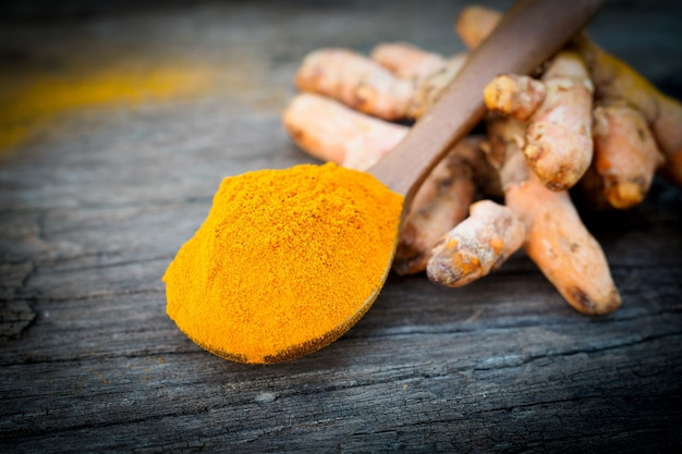 Turmeric powder and fresh turmeric in wooden spoon on old wooden table. herbs are native to southeast asia.