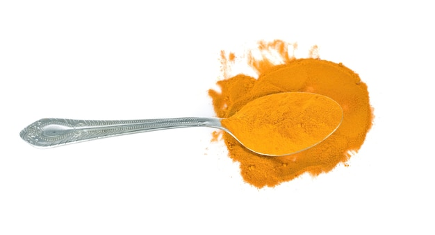 Turmeric powder in the  spoon isolated on white background.