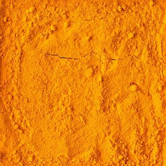 Turmeric powder texture background, top view, organic food