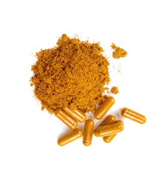 Turmeric powder and turmeric capsules on white background.top view