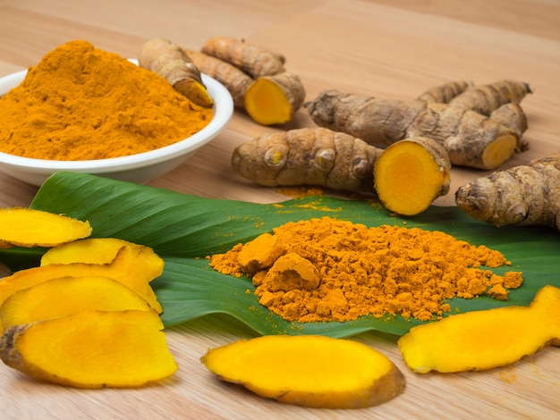 Turmeric powder and turmeric on old wooden background, herbal, s