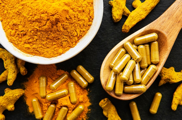 Turmeric powder and turmeric pills on a black concrete background