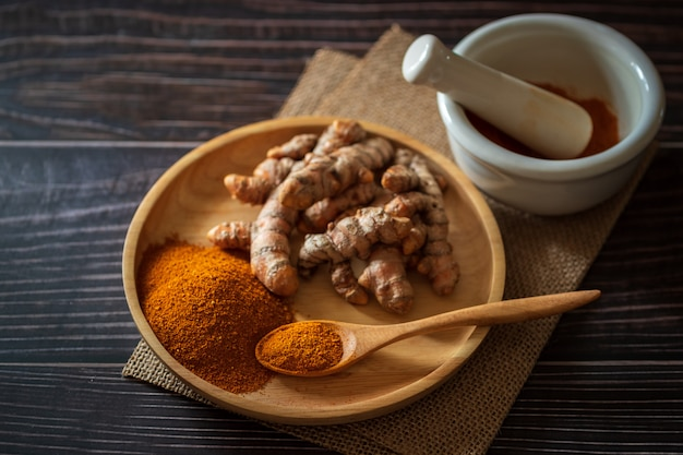 Turmeric powder and turmeric root on wooden dish
