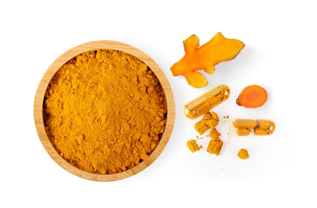 Turmeric powder in wood bowl isolated on white surface