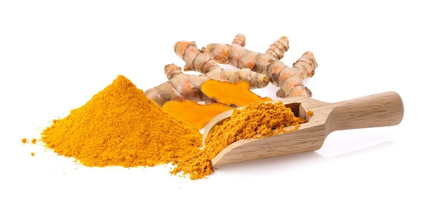 Turmeric powder in wood scoop isolated on white background. full depth of field