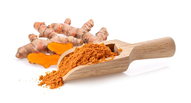 Turmeric powder in wood scoop  isolated on white
